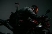Fotografie boční pohled na nebezpečný smíšený závod cyberpunk hráč v masce na koni motocykl na šedé