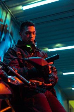 Selective focus of mixed race cyberpunk player near motorcycle looking at gun stock vector