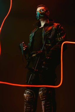 Dangerous bi-racial cyberpunk player in protective mask holding gun near neon lighting on black stock vector