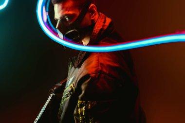 Selective focus of dangerous mixed race cyberpunk player in mask holding gun near blue neon lighting on black stock vector