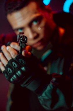 Selective focus of gun in hands of bi-racial cyberpunk player stock vector