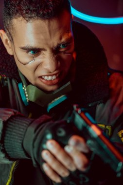 Selective focus of angry bi-racial cyberpunk player with metallic plates on face holding gun stock vector