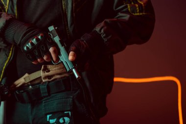 Cropped view of armed cyberpunk player with gun on black with neon lighting stock vector