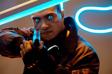 selective focus of handsome and mixed race cyberpunk player with metallic plates on face and blue eyes holding gun near neon lighting
