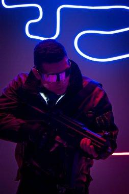 Armed mixed race cyberpunk player in futuristic glasses holding gun near neon lighting stock vector