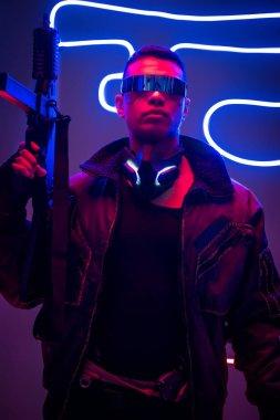 Dangerous mixed race cyberpunk player in futuristic glasses holding gun near neon lighting stock vector