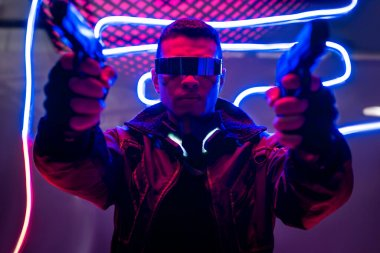 Selective focus of armed mixed race cyberpunk player in futuristic glasses holding guns near neon lighting stock vector