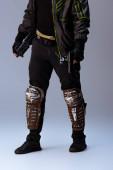 oříznutý pohled na kyberpunkového hráče držícího zbraň, když stojí na šedé