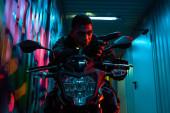 bi-rasszista cyberpunk játékos motorkerékpár célja fegyvert az utcán graffiti