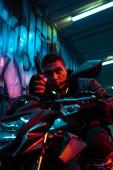 szelektív fókusz vegyes fajú cyberpunk játékos motorkerékpár célzás pisztoly az utcán graffiti