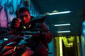 veszélyes és vegyes fajú cyberpunk játékos motorkerékpár célja fegyvert az utcán graffiti