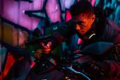smíšený závod cyberpunk hráč na motocyklu mířící pistole na ulici s graffiti