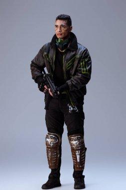 Handsome bi-racial cyberpunk player holding gun and standing on grey stock vector