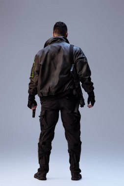 Back view of cyberpunk player holding gun and standing on grey stock vector