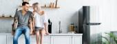 Panoramatický záběr tetovaného páru usmívat se na sebe, zatímco sedí na pracovní desce v kuchyni