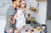Photo Side view of tattooed man touching beautiful blonde girlfriend near breakfast in kitchen