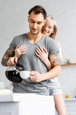 Selective focus of smiling woman embracing tattooed boyfriend pouring coffee in cup in kitchen stock vector
