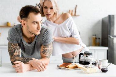 Beautiful woman looking at handsome tattooed boyfriend near breakfast on kitchen table stock vector