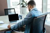 IT pracovník sedí před notebookem u stolu v pracovním prostoru