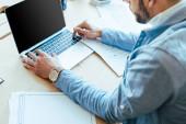 Oříznutý pohled pracovníka IT pomocí notebooku u stolu v pracovním prostoru