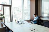 Vysokoúhlý pohled na pracovníka IT sedícího u stolu v prostoru pro spolupráci