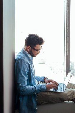 IT worker using laptop on windowsill near windows stock vector