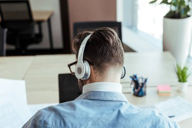 High angle view of IT worker with headphones in coworking space