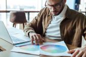Koncentrált UI designer néz papírok közelében laptop asztalnál coworking hely