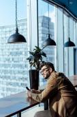 Důmyslný IT pracovník s chytrým telefonem u stolu v blízkosti oken v kooperačním prostoru
