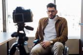 Selektivní zaměření handicapovaného bloggera na mluvení na invalidním vozíku před digitálním fotoaparátem