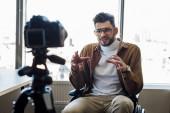 Selektivní zaměření handicapovaného bloggeru na bezbariérový rozhovor před digitálním fotoaparátem v blízkosti oken