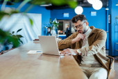 Selective focus of concentrated IT worker with laptop at table in coworking space