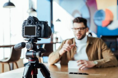 Selective focus of blogger in front of digital camera at table in coworking space stock vector