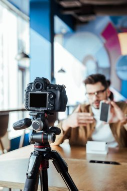 Selective focus of blogger in front of digital camera presenting smartphone in coworking space stock vector