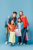 Fotografie aufgeregte Eltern und überraschte Kinder mit blauen Einkaufstüten