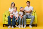 skeptičtí rodiče zavírající oči před dětmi při sledování filmu na pohovce s popcornem kbelík na žluté