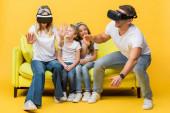 Lächelnde Kinder sitzen mit Eltern in Virtual-Reality-Headsets auf gelbem Sofa