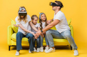 happy children sitting on sofa with parents in virtual reality headsets on yellow