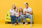 šťastná rodina v narozeninové párty čepice aplauding na pohovce na žluté
