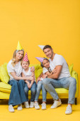 Fotografie cheerful family in birthday party caps hugging on sofa on yellow