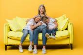 Fotografie těhotné matky objímání s úsměvem dcera a syn na pohovce na žluté
