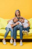 usmívající se těhotná matka objímání s šťastnou dceru a syna na pohovce na žluté