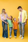 boldog család kéz a kézben a gyerekekkel a sárga