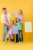 cheerful parents and excited kids with shopping bags on yellow