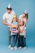 Fotografie glückliche Familie in Geburtstagskappen, Tochter hält Geschenkboxen auf blau