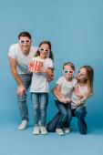 šťastná rodina sledování filmu v 3D brýle a držení popcorn kbelík na modré