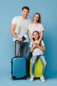 šťastná rodina s dcerou stojící s cestovními taškami, mapou, jízdenkami a pasy na modré