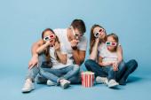 zmatená rodina v 3D brýle sledování filmu a držení popcorn kbelík na modré
