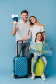 usmívající se rodiče a dcera s cestovními taškami, mapou, jízdenkami a pasy na modré