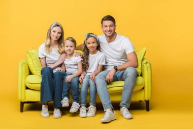 happy family sitting together on sofa on yellow